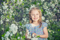 Happy little girl in cherry blossom garden Royalty Free Stock Image