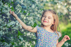 Happy little girl in cherry blossom garden Royalty Free Stock Photos