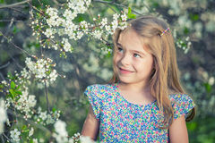Happy little girl in cherry blossom garden Royalty Free Stock Images