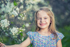 Happy little girl in cherry blossom garden Royalty Free Stock Image