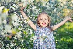 Happy little girl in cherry blossom garden Stock Image