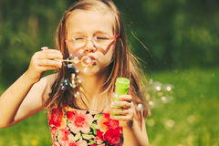 Happy little girl child blowing bubbles outdoor. Royalty Free Stock Image