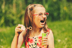 Happy little girl child blowing bubbles outdoor. Royalty Free Stock Photo