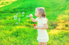 Happy little girl child blowing soap bubbles in summer Royalty Free Stock Photos