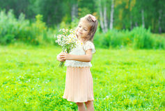 Happy little girl child with bouquet flowers in summer Stock Image