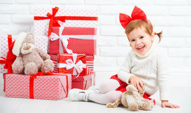 Happy little girl child with Christmas gifts at wall Royalty Free Stock Images