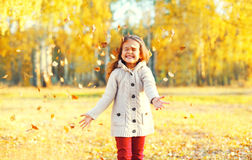 Happy little girl child having fun playing with yellow leafs in sunny autumn Stock Image