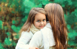 Happy little girl child hugging mother in winter Royalty Free Stock Images