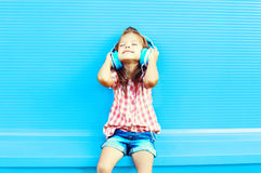 Happy little girl child listens to music in headphones royalty free stock images