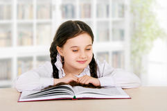 Happy little girl child reads book indoor Stock Photos