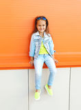 Happy little girl child wearing a sunglasses and jeans clothes Royalty Free Stock Photos