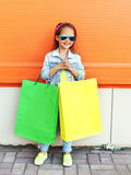 Happy little girl child wearing a sunglasses and jeans clothes with shopping bags Stock Images