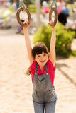 Happy little girl on children playground. Summer, childhood, leisure and people concept - happy little girl hanging on gymnastic rings at children playground Stock Photography