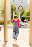 Happy little girl on children playground. Summer, childhood, leisure and people concept - happy little girl hanging on gymnastic rings at children playground Royalty Free Stock Photography