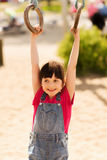 Happy little girl on children playground. Summer, childhood, leisure and people concept - happy little girl hanging on gymnastic rings at children playground Stock Images