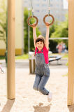 Happy little girl on children playground. Summer, childhood, leisure and people concept - happy little girl hanging on gymnastic rings at children playground Stock Photo