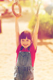 Happy little girl on children playground. Summer, childhood, leisure and people concept - happy little girl hanging on gymnastic rings at children playground Royalty Free Stock Photos