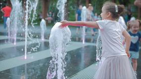 Happy little girl in the city playing with water in fountains, happy and carefree childhood, the concept of freedom and stock video