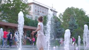 Happy little girl in the city playing with water in fountains, happy and carefree childhood, the concept of freedom and stock footage