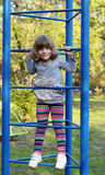Little girl climb on park playground Stock Photos