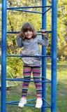 Little girl climb on park playground Stock Photos