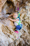 Happy little girl climbing on cliff Royalty Free Stock Photography