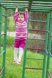 Happy little girl climbing on outdoor playground Royalty Free Stock Image