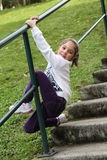 Happy little girl climbing railing Stock Photography