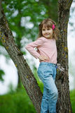 Happy little girl climbing to the tree Stock Photo