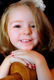 Happy Little Girl. A closeup of a happy little blond bright eyed cute 5 year old girl with a bow in her hair and red painted fingernail polish. Shallow depth of royalty free stock photography