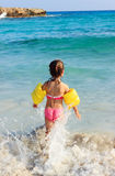 Happy little girl on the coast of tropical sea Royalty Free Stock Photo