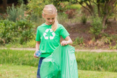 Happy little girl collecting rubbish. On a sunny day Stock Images