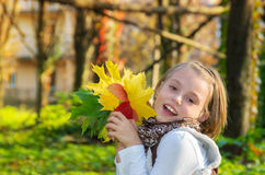 Happy little girl with colored maple leaves. Royalty Free Stock Image
