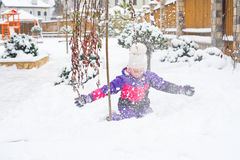 Happy little girl in colorful suit and white hat play with snow Stock Photos
