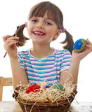 A happy little girl coloring easter eggs. White background Royalty Free Stock Photos