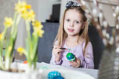 A happy little girl coloring easter eggs Royalty Free Stock Image