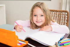 Happy little girl colouring at the table Royalty Free Stock Images