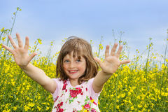 Happy little girl on a colza field Royalty Free Stock Images