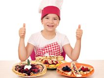 Little girl cook with crepes and thumbs up Royalty Free Stock Photography