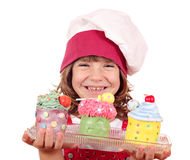Happy little girl cook with cupcakes Royalty Free Stock Image
