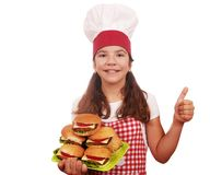 Little girl cook with hamburgers and thumb up Royalty Free Stock Photos