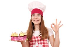 Little girl cook with muffins and ok hand sign Royalty Free Stock Photos