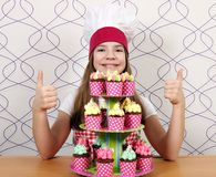 Little girl cook with muffins and thumbs up Stock Photography