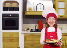 Happy little girl cook with spaghetti in kitchen Royalty Free Stock Images