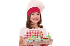 Little girl cook with sweet muffins decorated as spring flowers. Happy little girl cook with sweet muffins decorated as spring flowers stock photo
