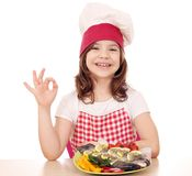 Little girl cook with trout on plate and ok hand sign Royalty Free Stock Photography