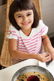 Happy little girl cooking a chocolate chip cake Stock Image