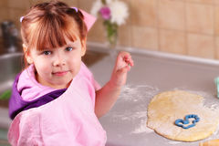 Happy little girl cooks biscuits in the kitchen Stock Photos