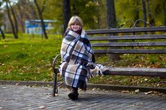 Happy little girl covered with blanket sit on bench. In spring day Stock Photography