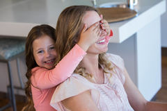 Happy little girl covering her mother eyes Royalty Free Stock Images